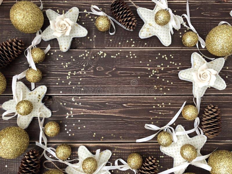 Fondo de madera con las bolas, las estrellas y los conos de oro del pino imagenes de archivo