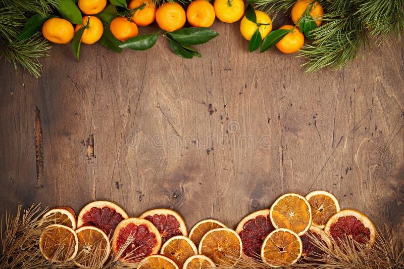 Fondo de madera con las ramas y las naranjas del abeto foto de archivo