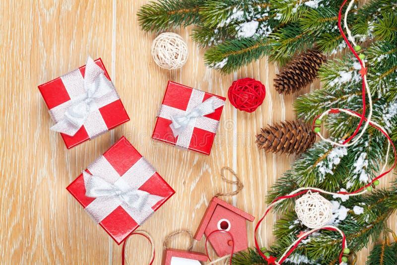 Fondo de madera de la Navidad con el árbol de abeto de la nieve y la decoración fotos de archivo