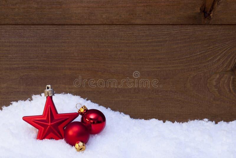 Fondo de madera de la Navidad en nieve, bolas rojas y la estrella fotografía de archivo libre de regalías