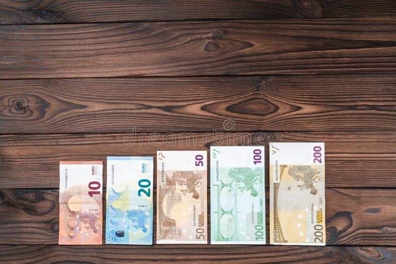 Fondo de madera, dinero de diverso valor, pasos en el crecimiento de la carrera, sueldo por hora Visión superior fotos de archivo