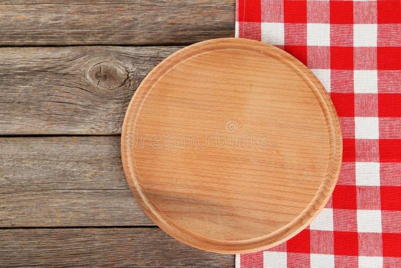 Fondo de madera gris con la servilleta con la tabla de cortar foto de archivo libre de regalías