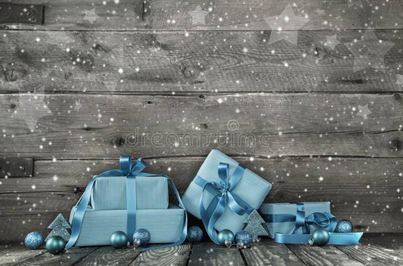Fondo de madera gris de la Navidad con una pila de presentes en azul foto de archivo