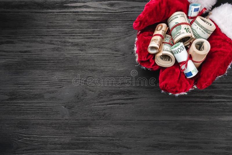 Fondo de madera negro Las manos de Papá Noel por completo del dinero Tarjeta de Navidad Visión superior Enhorabuena de Navidad imagenes de archivo