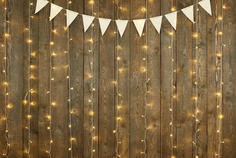 Fondo de madera oscuro con las luces y las banderas, contexto abstracto del día de fiesta, espacio de la copia para el texto fotos de archivo