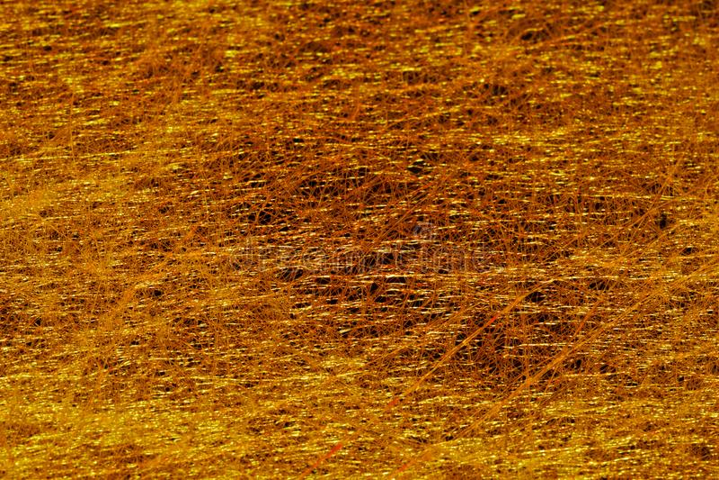 Fondo de oro del fieltro fino en un fondo oscuro con un modelo caótico imagenes de archivo