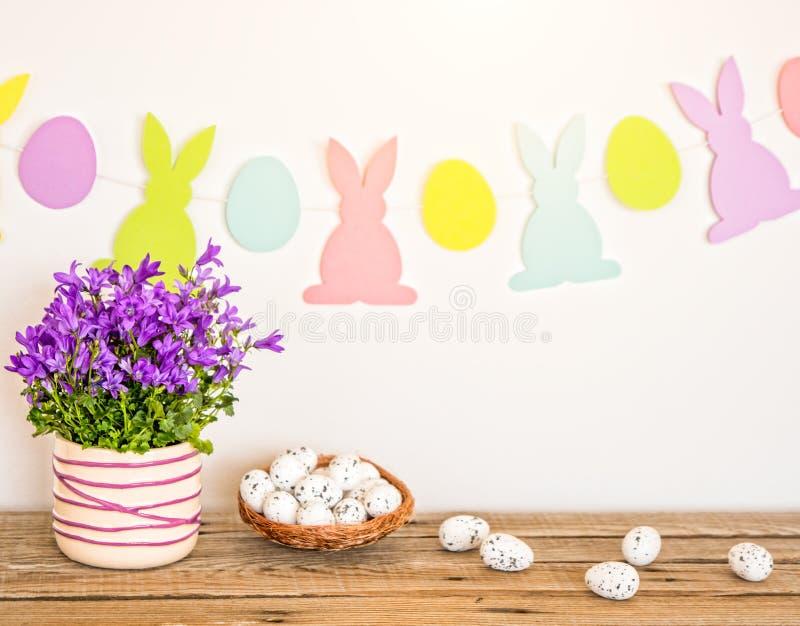 Fondo de Pascua con los conejitos guirnalda, las flores de la primavera y los huevos en la tabla de madera imagen de archivo