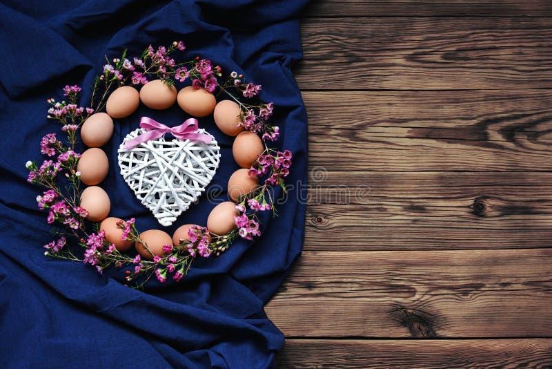 Fondo de Pascua con los huevos en lona azul y la tabla de madera fotos de archivo