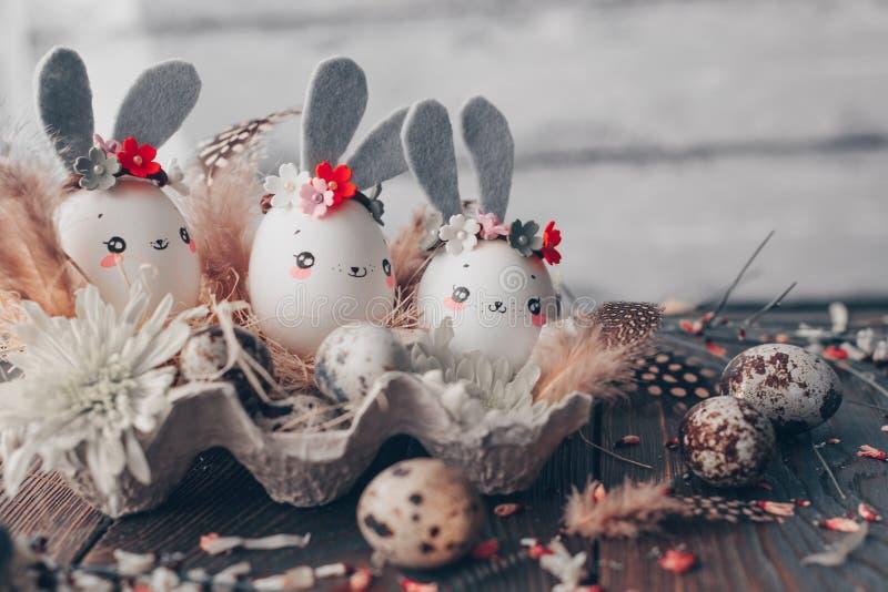 Fondo de Pascua, conejos hechos en casa de las cáscaras de huevo y crisantemo amarillo en cajas de cartón imagen de archivo