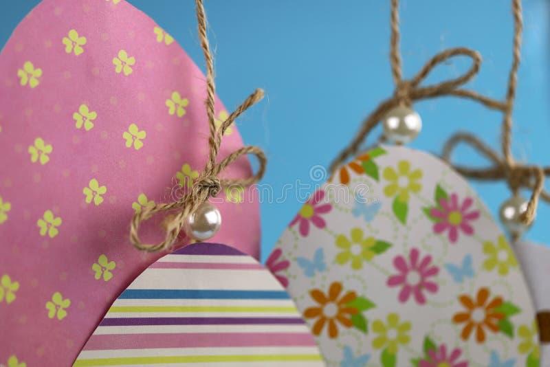 Fondo de Pascua hecho a mano Grupo de huevos coloreados hechos de la caída de papel en una cuerda en un fondo azul imagen de archivo libre de regalías