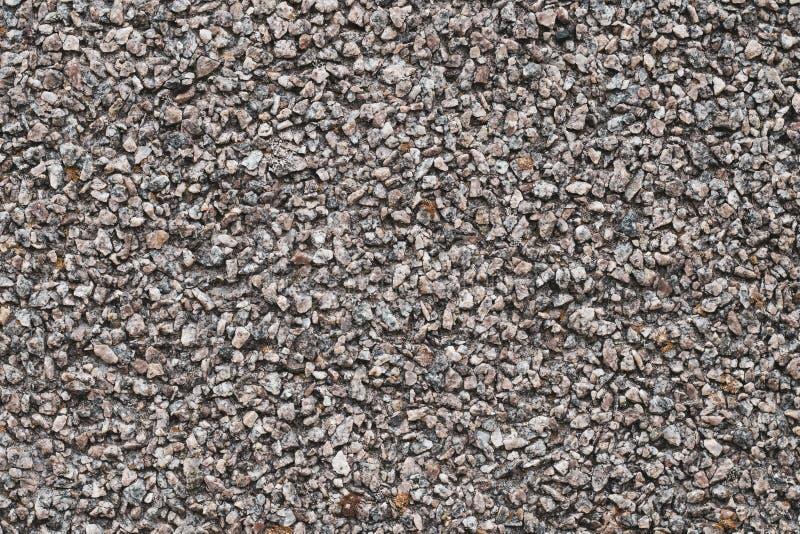 Fondo de pequeños guijarros marrones y grises Pared de piedra áspera, modelo abstracto Superficie, textura de la roca foto de archivo