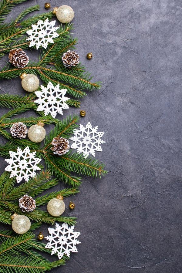 Fondo de piedra oscuro de la Navidad con la rama de un árbol de abeto, de los conos del pino y de los copos de nieve Endecha plan fotografía de archivo