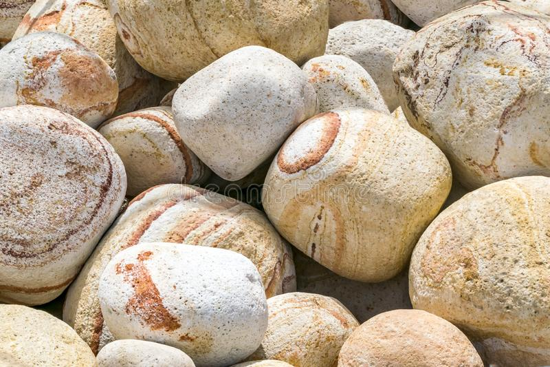 Fondo de piedra redondo y oval del arco iris rayado grande amarillo y blanco de Brown de la pila Material decorativo ambiental na fotografía de archivo libre de regalías