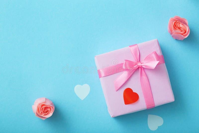 Fondo de regalos con los corazones del confeti y de rosas, cajas envueltas en documento decorativo sobre el fondo azul coloreado  imagen de archivo