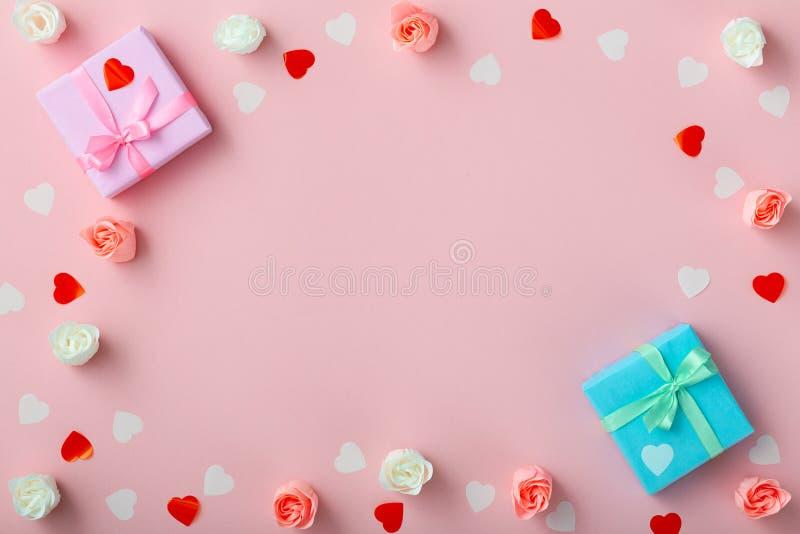 Fondo de regalos con los corazones del confeti y de rosas, cajas envueltas en documento decorativo sobre el fondo rosado coloread imagen de archivo