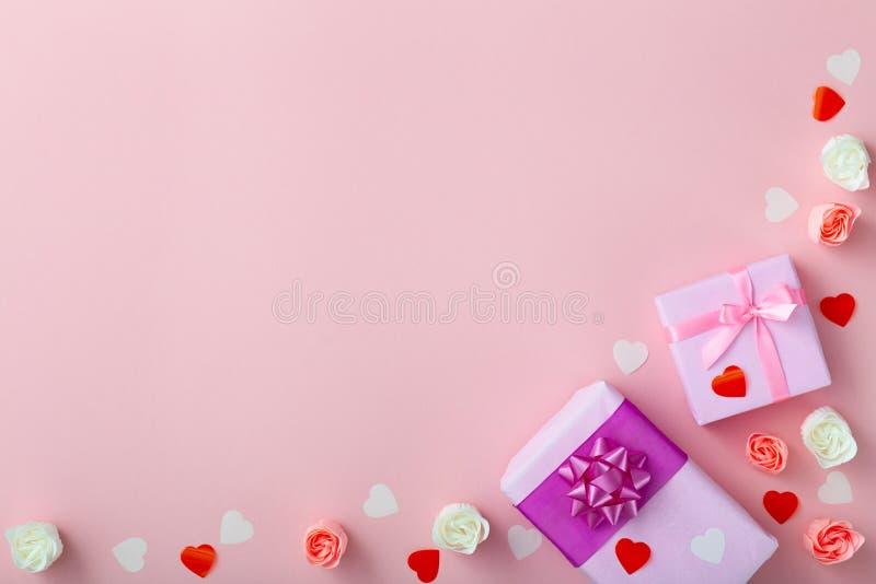 Fondo de regalos con los corazones del confeti y de rosas, cajas envueltas en documento decorativo sobre el fondo rosado coloread fotos de archivo libres de regalías