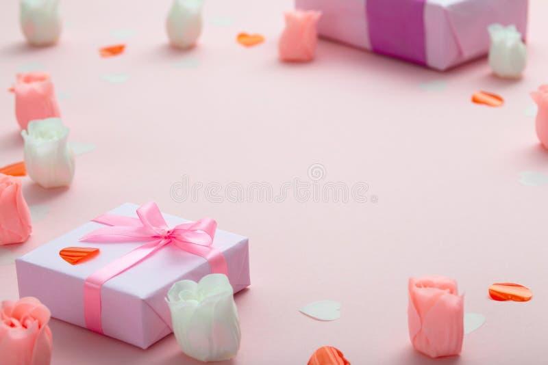 Fondo de regalos con los corazones del confeti y de rosas, cajas envueltas en documento decorativo sobre el fondo rosado coloread fotos de archivo