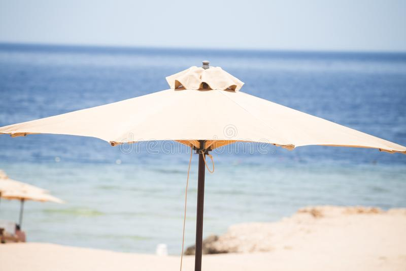 Fondo de relajaci?n de la playa con los paraguas y el mar fotos de archivo