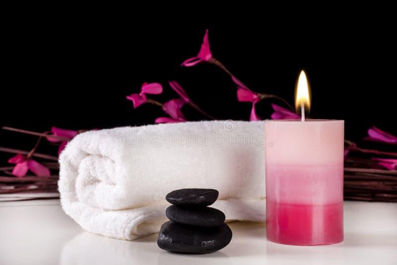Fondo decorativo del balneario con la vela aromática que quema en la tabla y las piedras blancas del toalla y negras imagen de archivo libre de regalías