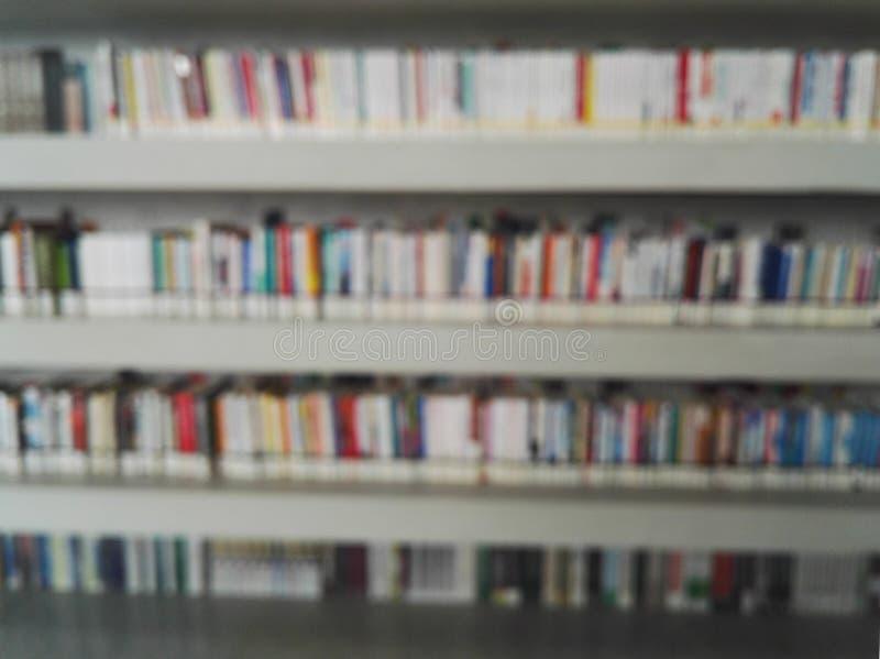 Fondo degli scaffali per libri della sfuocatura nella biblioteca fotografia stock libera da diritti