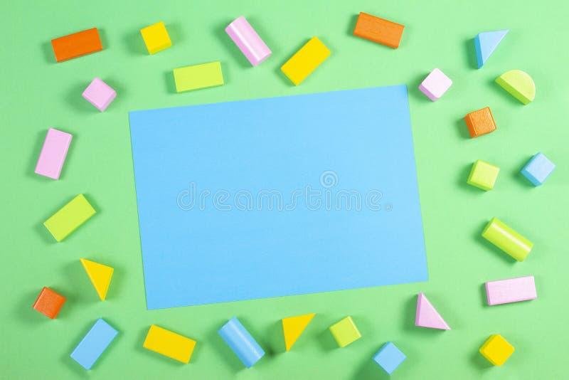 Fondo dei giocattoli con la carta blu in bianco e modello di legno variopinto dei cubi sul fondo di colore verde fotografia stock