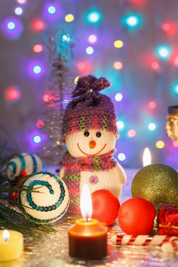 Fondo del Año Nuevo con un muñeco de nieve, los vidrios y las velas fotografía de archivo libre de regalías