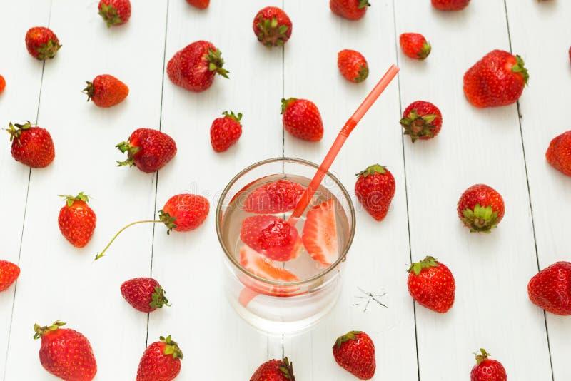 Fondo del agua de la fresa y de las bayas frescas en una tabla blanca Bebida del verano fotografía de archivo