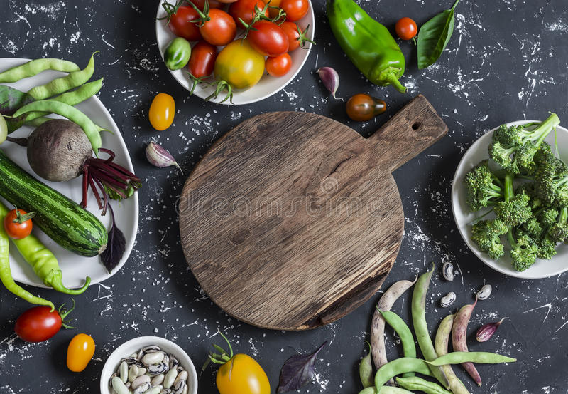 Fondo del alimento Surtido de verduras frescas alrededor de la tabla de cortar en un fondo oscuro Visión superior imágenes de archivo libres de regalías