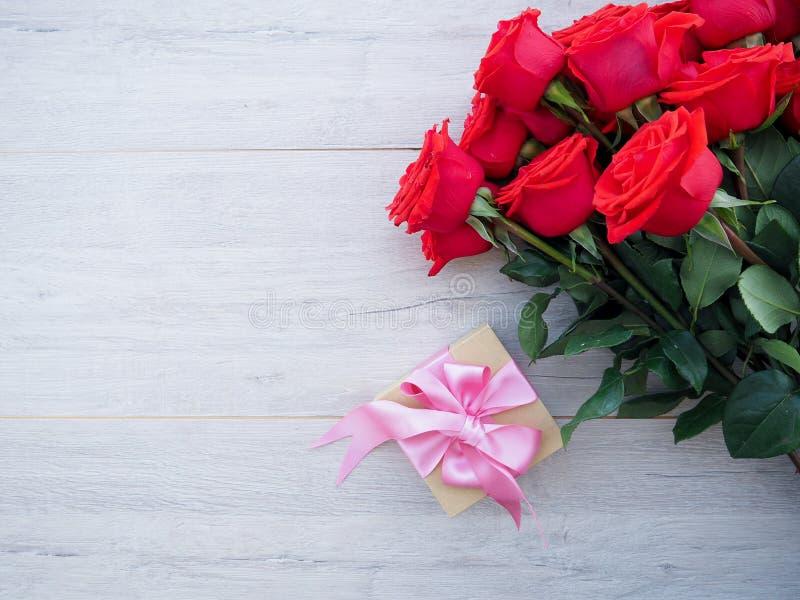 Fondo del biglietto di S. Valentino del contenitore di regalo con il nastro e l'arco e mazzo di rose rosse su legno Spazio per la fotografie stock libere da diritti