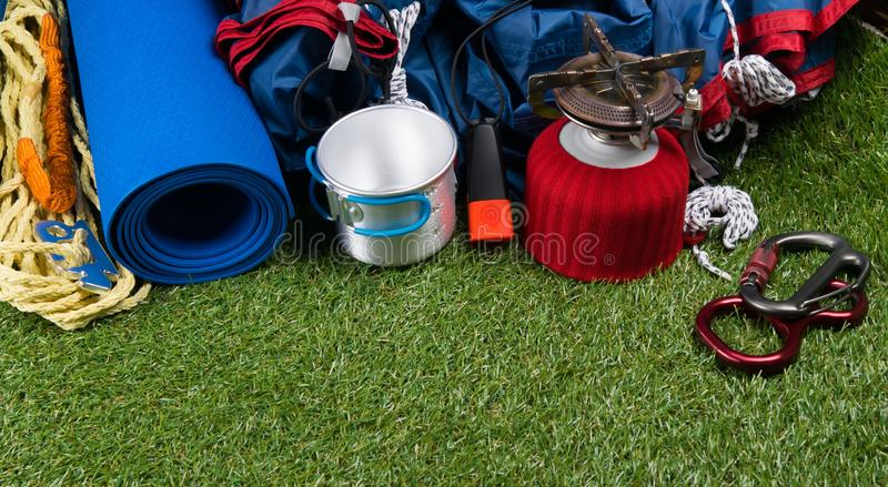 Fondo del césped equipo de viaje para las actividades al aire libre, tienda, mechero de gas, carabinas de la taza, y cuerda, y es fotos de archivo libres de regalías