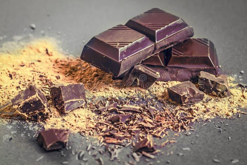 Fondo del chocolate Pedazos rotos chocolate y polvo de cacao dispersado en un fondo negro Primer oscuro del chocolate foto de archivo