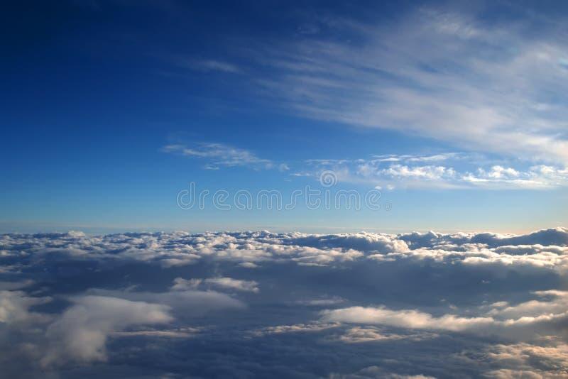 Fondo del cielo azul sobre las nubes de cúmulo con los rayos del sol poniente fotos de archivo libres de regalías