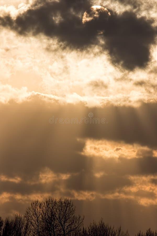 Fondo del cielo di tramonto, Sun dietro la nuvola scura con Ra crepuscolare fotografie stock libere da diritti