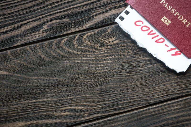 Fondo del concepto Coronavirus Pasaporte y nota COVID-19 coronavirus sobre mesa de madera oscura Brote de virus de la corona nove foto de archivo libre de regalías