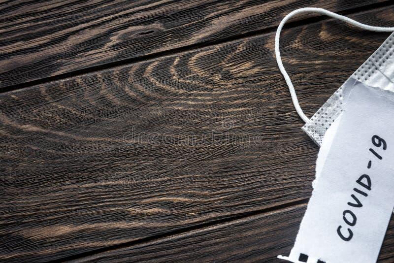 Fondo del concepto Coronavirus Vista superior de la nota COVID-19 coronavirus y máscara médica protectora sobre mesa de madera os imagen de archivo