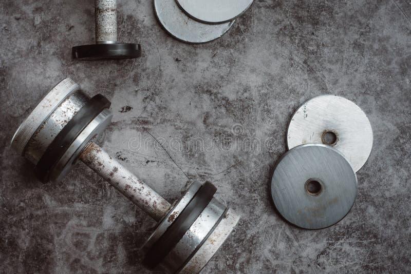Fondo del concepto de la aptitud o del levantamiento de pesas Viejas pesas de gimnasia del hierro en el gris, piso del conrete en imagenes de archivo