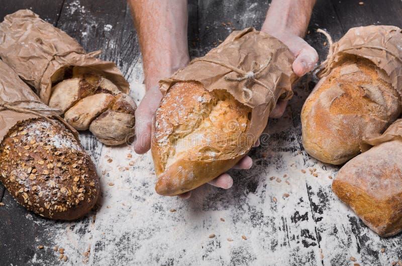 Fondo del concepto de la panadería Pan del pan del control de las manos imagen de archivo libre de regalías