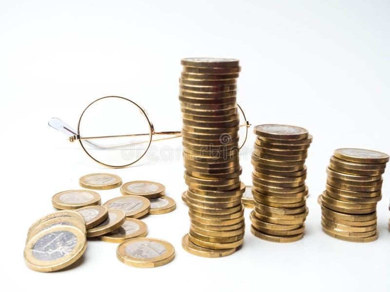 Fondo del concepto financiero y que considera con las pilas de la moneda, vidrios, conceptos del foco selectivo de la gesti?n fis fotos de archivo