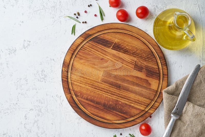 Fondo del condimento dell'alimento Tagliere di legno rotondo, spezie, erbe sul contesto concreto bianco Vista superiore, spazio d immagine stock libera da diritti