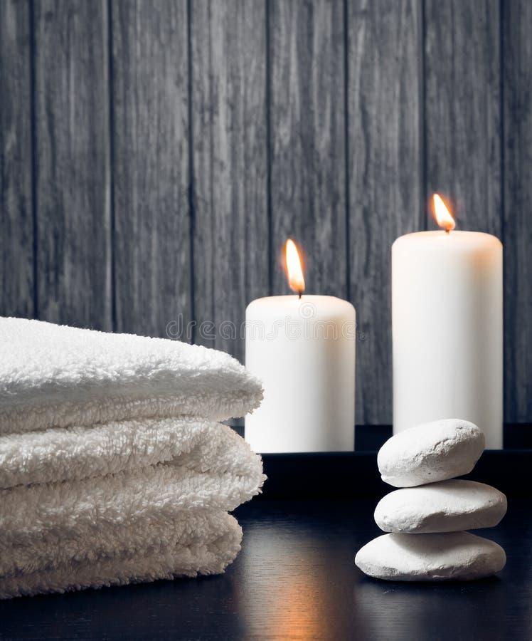 Fondo del confine di massaggio della stazione termale con l'asciugamano impilato Candele e pietra fotografia stock