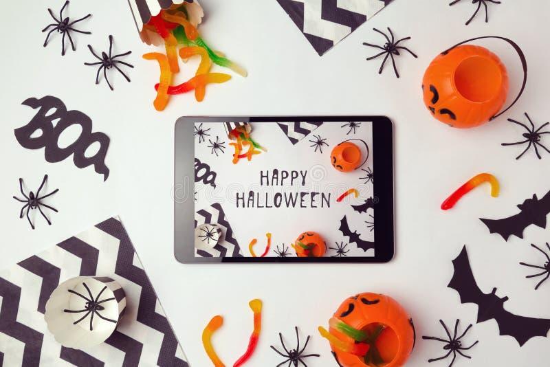Fondo del día de fiesta de Halloween con la tableta digital foto de archivo