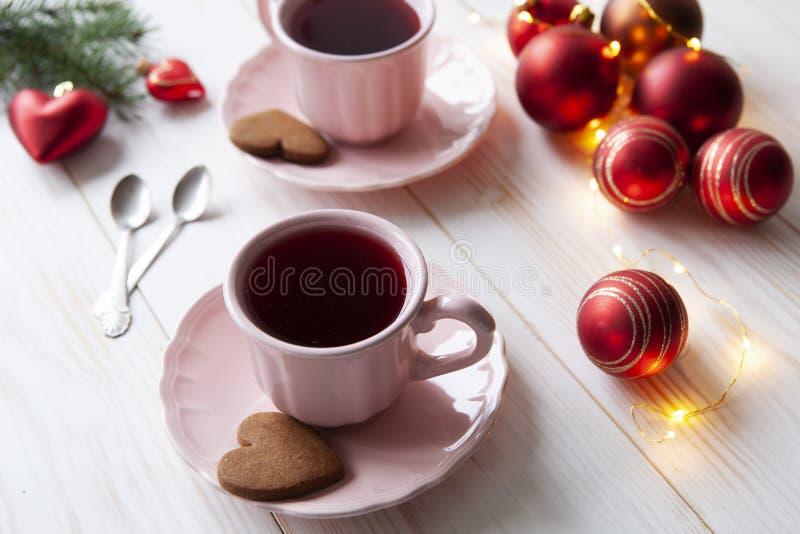 Fondo del día de fiesta de la Navidad con dos tazas de té y de galletas imagen de archivo