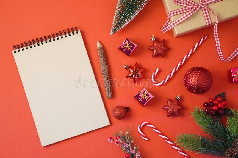 Fondo del día de fiesta de la Navidad con el cuaderno y decoraciones en la tabla roja fotografía de archivo