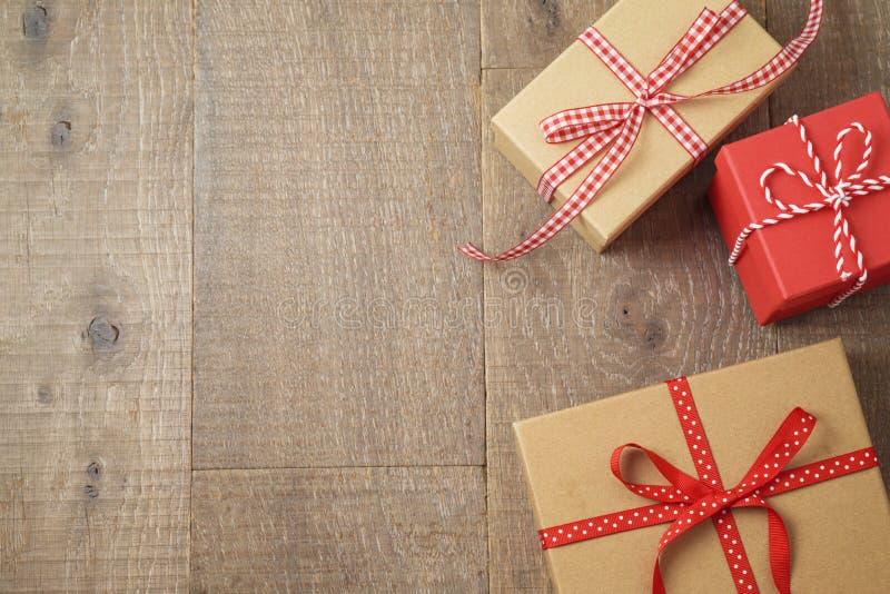 Fondo del día de fiesta de la Navidad con las cajas de regalo en la tabla de madera fotos de archivo