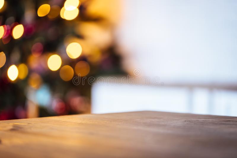 Fondo del día de fiesta de la Navidad con la tabla rústica vacía y el bokeh de la sala de estar con el árbol de navidad imágenes de archivo libres de regalías