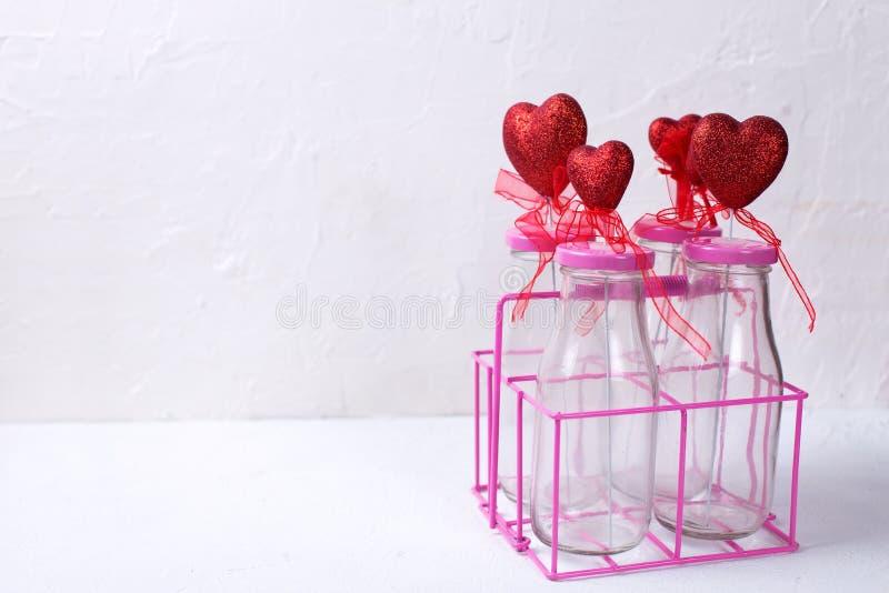 Fondo del día de San Valentín del St Frontera de corazones rojos coloridos en botellas en el fondo texturizado blanco foto de archivo
