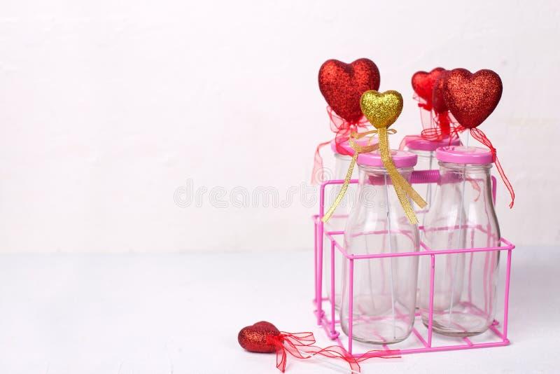 Fondo del día de San Valentín del St Frontera de corazones rojos y de oro coloridos en botellas en el fondo texturizado blanco fotos de archivo libres de regalías