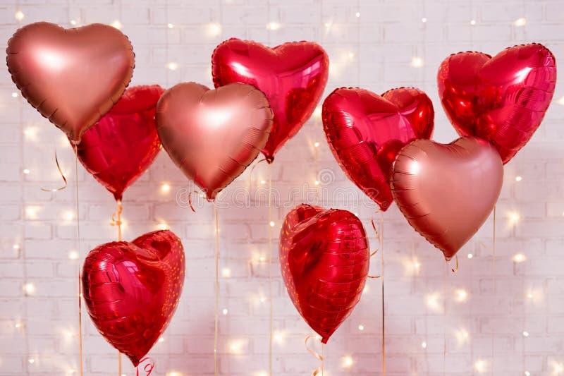Fondo del día de tarjeta del día de San Valentín - grupo de globos en forma de corazón rojos sobre la pared de ladrillo foto de archivo