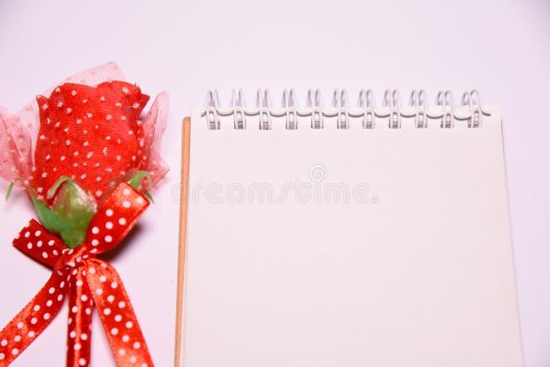 Fondo del día de tarjetas del día de San Valentín Rosa roja en la libreta en blanco para el espacio de la copia en el blackground fotografía de archivo