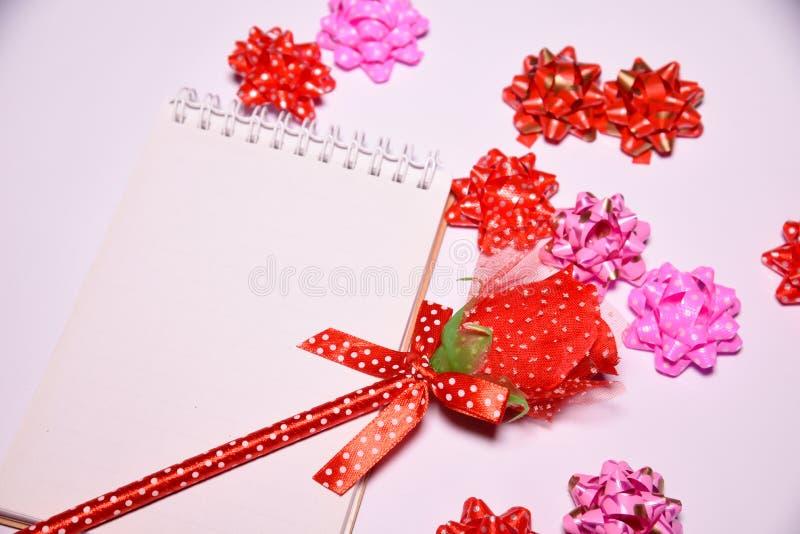 Fondo del día de tarjetas del día de San Valentín Rosa roja en la libreta en blanco para los lazos de satén del espacio y de la c foto de archivo